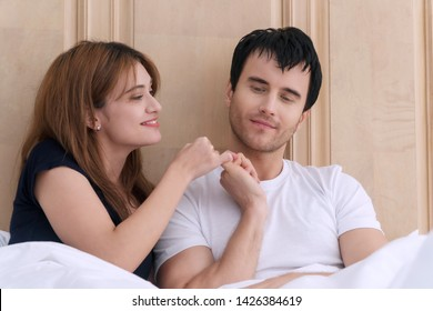 Concept of promise. Happy Young couples holding hand together at home. Young woman trying to reconcile her boyfriend after problem on the bed hands reconcile with clasping each other's little finger.