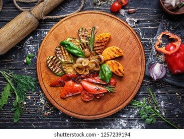 Concept promotional flyer. Vegetables roasted on a grill decorated with basil leaves. On a black wooden background. Flay lay. Top view