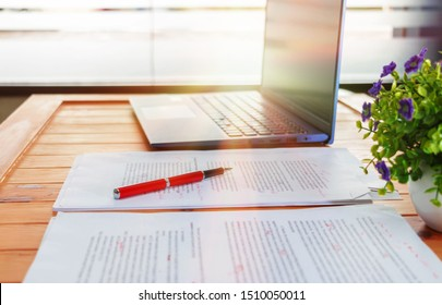 concept of proofreading with pen, blur text and laptop on desk in office
