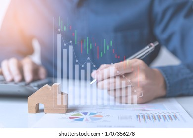 Concept of Property investment and house mortgage financial. A business man, agent calculating income, sales,  or house dept while economy crisis effect from Coronavirus pandemic. Stock market graph.