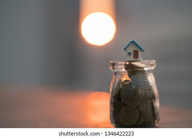 Concept for property ladder, mortgage and real estate investment. House models on top of coins jar with sunset backgrounds.