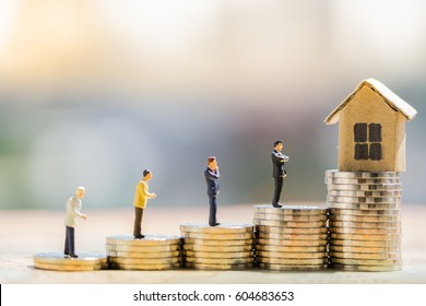 Concept for property ladder, mortgage and real estate investment. house model and miniature businessman on coins stack.
