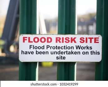 Concept of protection from flooding or area of flood risk shown by sign saying 'Flood Risk Site - flood protection works have been undertaken on this site' on a green fence by electricity substation