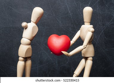 Concept protection of handicapped people. Wooden figure of healthy man gives another physically disabled figure without hands a big red heart as a symbol of love and care.