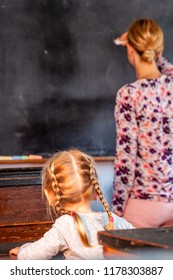 Concept of public primary school education with young girl listening to the female teacher.