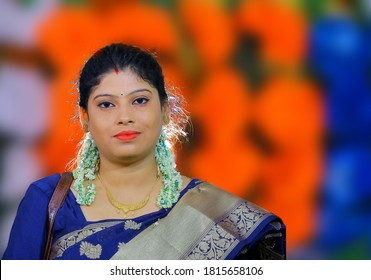 Concept of Puja advertisement. Portrait of a beautiful, traditional, Indian woman who wear a blue saree against with try color background. Puja fashion. Selective focus concept.