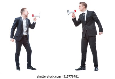 Concept of quarrel or politics debate.Two angry stressed businessman are shouting on each other with megaphones. Full length studio portrait isolated on white.