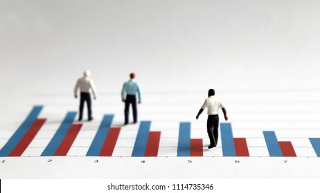 The concept of racial discrimination in employment and promotion. The miniature men standing on a bar graph.
