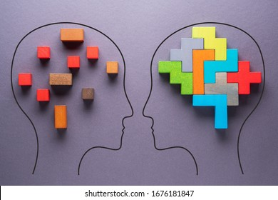 The concept of rational and irrational thinking of two people. Heads of two people with colourful shapes of abstract brain for concept of idea and teamwork on gray background. Different thinking.