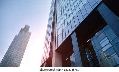 Concept for real estate and corporate construction..The modern office building of the orange morning sun in the sky background.