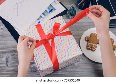 Concept of receiving and preparing presents at Christmas, secret santa concept. Top above overhead view photo of woman's hands opening a big present box on her desktop