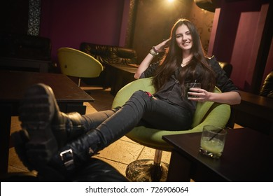 Concept: recreation, millennial, nightlife. Beautiful young woman relax in empty underground night club.