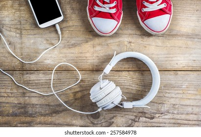Concept with red sneakers and tablet with white headphones laid on wooden floor background.