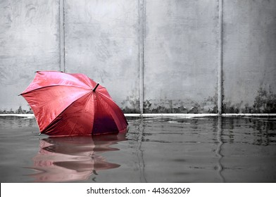 Concept of red umbrella floating on flooded street and waiting for help me after the rain.