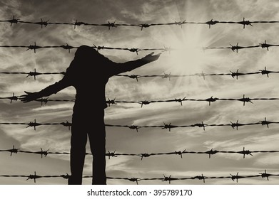 Concept of refugee. Silhouette of a refugee child near the fence of barbed wire