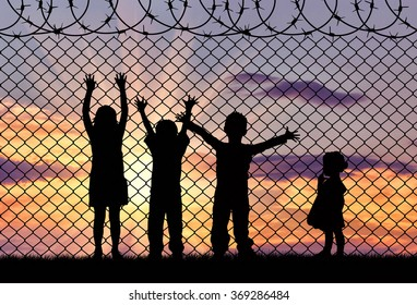 Concept of refugee. Silhouette of the hungry children of refugees near the border fence in the sunset