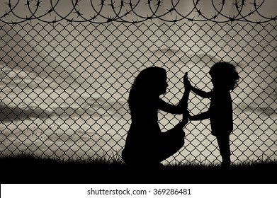 Concept of refugee. Silhouette of mother and child refugees at the border fence at sunset