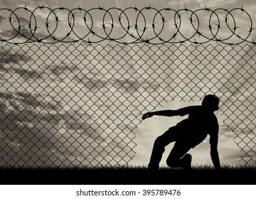 Concept of the refugees. Silhouette of refugees crossed the border illegally through the hole in the fence