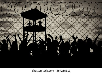 Concept of the refugees. Silhouette of a crowd of refugees at the border against the sunset and the guard tower