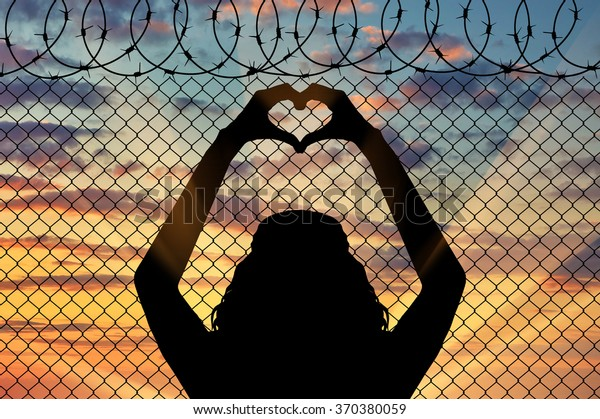 Concept of the refugees. Silhouette of a refugee shows a gesture from the hands of the heart on the background of the fence near the border