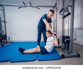 Concept of rehabilitation. Young boy doing exercises on mat under supervision of physiotherapist. Exercise therapy