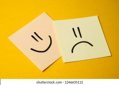 The concept of the relationship of colleagues at work in the office. Yellowish stickers with faces of joy and sadness on a yellow background.