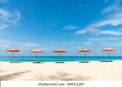 Concept of relax on tropical resort beach with parasol sunshades on sand in line with blue sea and sky on background