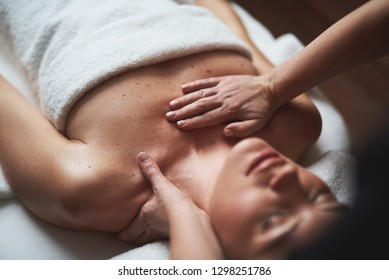Concept of relaxation and body care. Close up portrait of female therapist making decollete massage to young woman relaxing on couch in spa salon