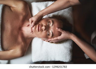 Concept of relaxation and body care. Top view portrait of female therapist making relaxing anti-age massage of face to young woman in spa salon