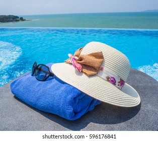 Concept of relaxing day: A wicker hand made beach hat with blue towel and sunglasses on the pool side in the sunny day.