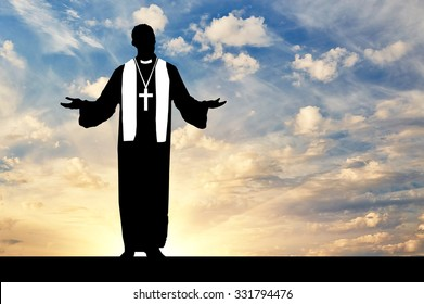 Concept of religion. Priest praying silhouette against the evening sky in the sun