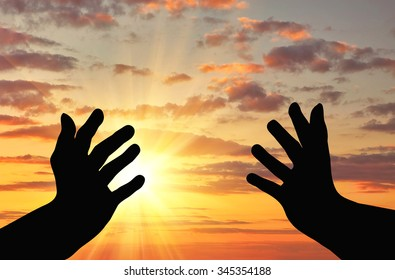 Concept of religion is a refugee. Silhouette of praying hands of an appeal to the sky