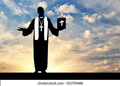 concept of religion. Silhouette of a priest praying with the Bible in his hand against the evening sky in the sun