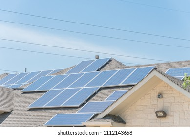 Concept of renewable clean vs. traditional energy. Close-up solar panel system on asphalt shingles rooftop and electrical wires. Rail-less racking battery storage at Grapevine, Texas, USA blue sky