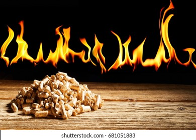 Concept of renewable natural wood fuel for alternative energy with flames burning behind a pile of wood pellets with copy space