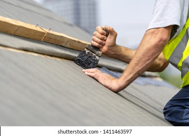 Concept of renovation, repair and fixing frame work house. Close up, cropped photo of roofer recovering roof. Man working with tar, spatula and special waterproof bitumen membrane on modern building