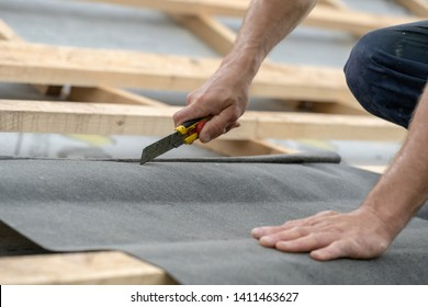 Concept of renovation, repair, fixing frame work house. Cropped, close up photo of mature contractor working with stapler and waterproof bitumen membrane on rooftop of new modern building construction