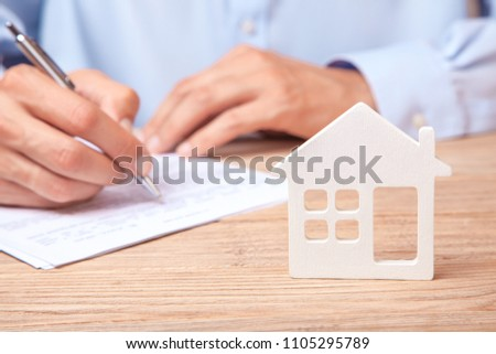 The concept of renting a home, credit or insurance. Man in shirt signs  contract against the background of the house