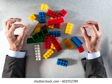 concept of reorganization or restructuring with zen businessman hands facing a group of messy plastic blocks on his desk for team building or corporate redevelopment, flat lay view