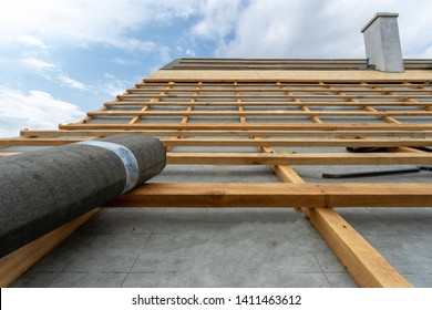 Concept of residential building under construction. Vertical photo of unfinished wooden roof top with special waterproof bitumen membrane of new modern house