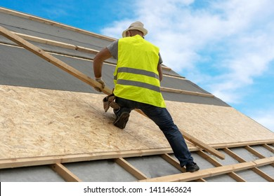 Concept of residential building under construction. Professional and qualified roofer in protective uniform wear installing wooden plank on rooftop of new modern house against blue sky on background