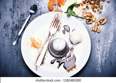 Concept: restaurant menu, healthy eating, homemade and gourmands. White plate with chocolate fondant with orange noodles and ice cream on messy vintage grey background. Nuts and butter decor