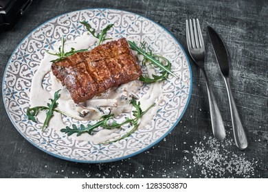 Concept: restaurant menu, healthy food, homemade, gourmet, gluttony. plate with steak and mushroom sauce on a weathered wooden table. Top down view. Close-up.