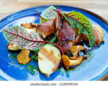 Concept: restaurant menus, healthy eating, homemade, gourmands, gluttony. White plate of pork medallions  with mushroom sauce on weathered wooden table. side-view, roasted pork fillet - tenderloin