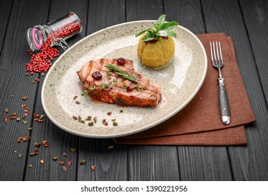 Concept: restaurant menus, healthy eating, homemade, gourmands, gluttony. Pork steak on the bone with cherry-ginger sauce with ingredients on messy sackcloth background.