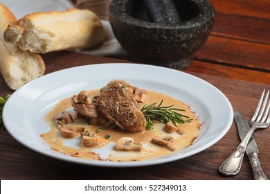 Concept: restaurant menus, healthy eating, homemade, gourmands, gluttony. White plate of pork medallions with mushroom sauce on weathered wooden table.