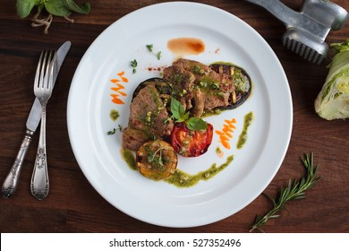 "Concept: restaurant menus, healthy eating, homemade, gourmands, gluttony. White plate of veal medallions with grilled vegetables and ""pesto"" sauce with ingredients on vintage background. Top-down"
