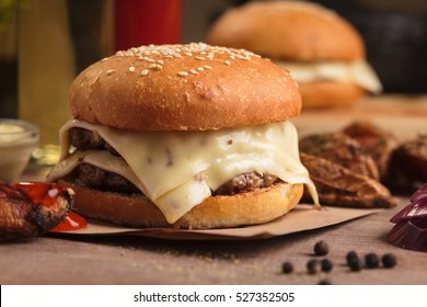Concept: restaurant menus, healthy eating, homemade, gourmands, gluttony. Classic double cheeseburger with ingredients, drinks and potato wedges on messy vintage wooden background.