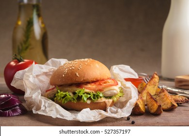 Concept: restaurant menus, healthy eating, homemade, gourmands, gluttony. Classic burger with chicken with ingredients and potato wedges on messy vintage wooden background.