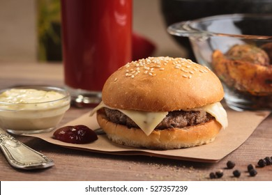 Concept: restaurant menus, healthy eating, homemade, gourmands, gluttony. Classic cheeseburger with ingredients, drinks and potato wedges on messy vintage wooden background.
